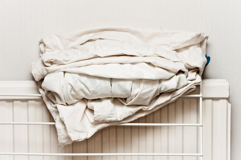 Bed sheets. White cotton bed sheets folded on a home radiator stock image
