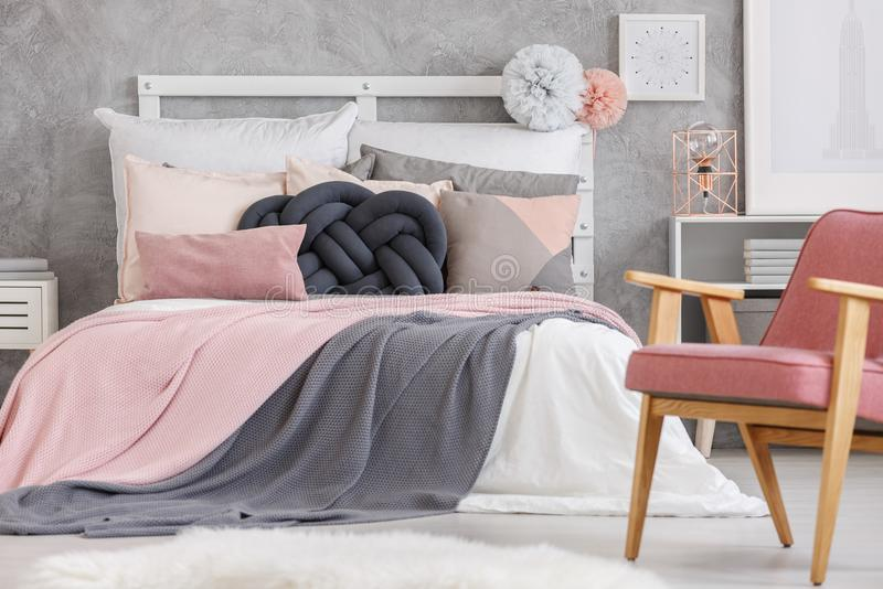 Bed with soft color bedsheets. Pastel pompons on bolster of king-size bed with soft color bedsheets in stylish bedroom with pink chair royalty free stock images