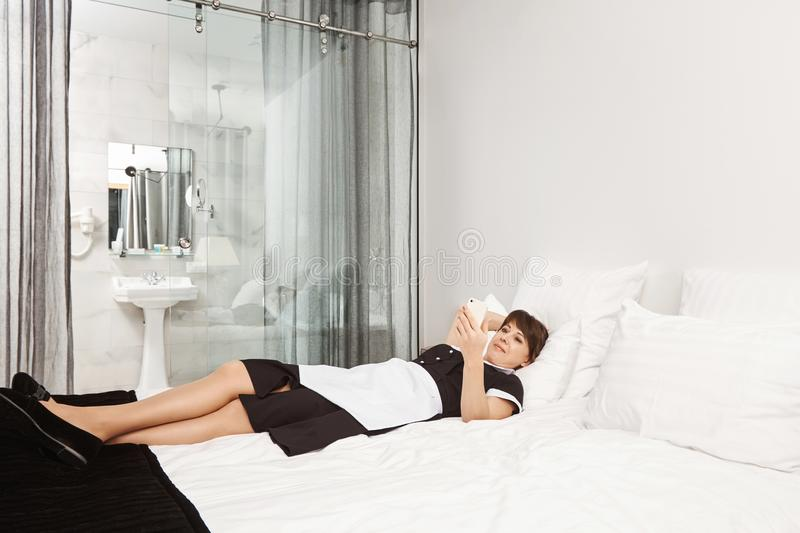 Bed is so soft and comfortable. Portrait of housemaid violating rules and lying on bedroom in hotel room, browsing or royalty free stock photography
