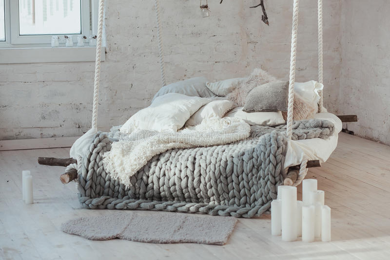 The bed suspended from the ceiling. Grey big cozy blanket knit. Scandinavian style, gray plaid, candles. stock photo