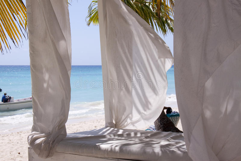 Bed on tropical beach. Comfortable bed shaded with white drapes on idyllic tropical beach, Bounty Island, Dominican Republic royalty free stock photo
