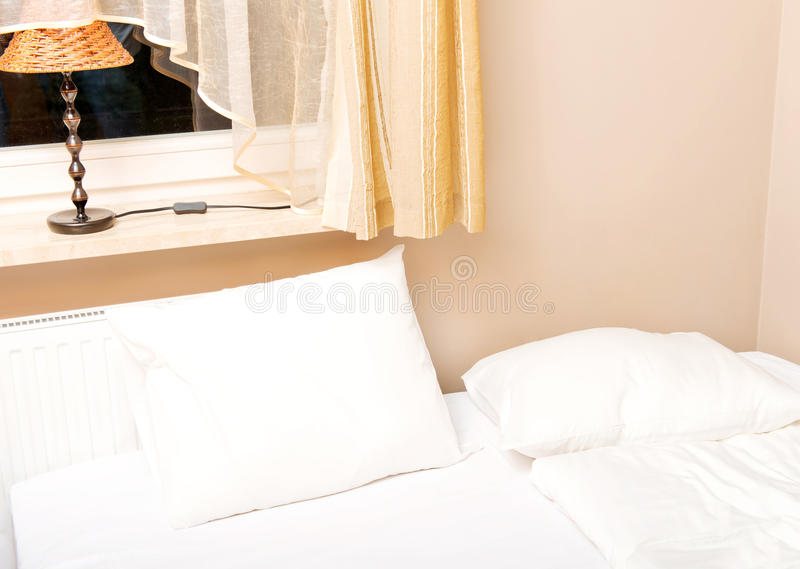 Bed with white bedclothes and brown bedcover.  royalty free stock image