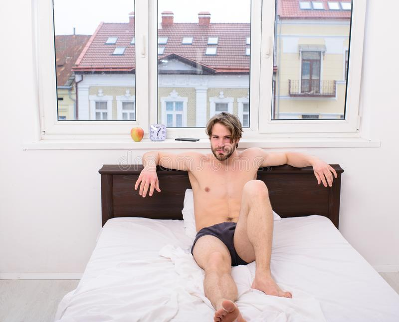 Bed with white bedclothes and nude man. Morning habits concept. Macho relaxing in bedroom. Morning routines that will. Set up each day. Macho guy underpants royalty free stock image