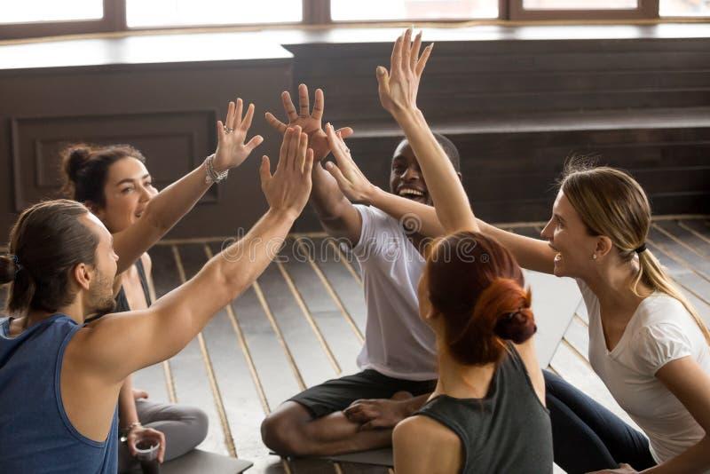 Bedachtzame gelukkige sportieve diverse mensen die bij handen aansluiten zich bij groepssemin stock afbeelding