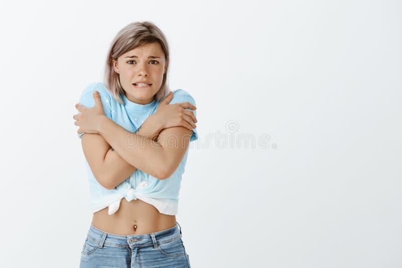 Bedarfsaufwärmen, ist es kühl Porträt der netten europäischen Studentin im stilvollen T-Shirt, in beißender Lippe und im Die Stir lizenzfreie stockfotografie