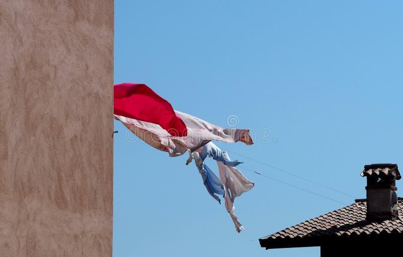 Bedbladen en kleren die uit op een drooglijn tussen dak en muur, in een winderige dag hangen te drogen stock foto's