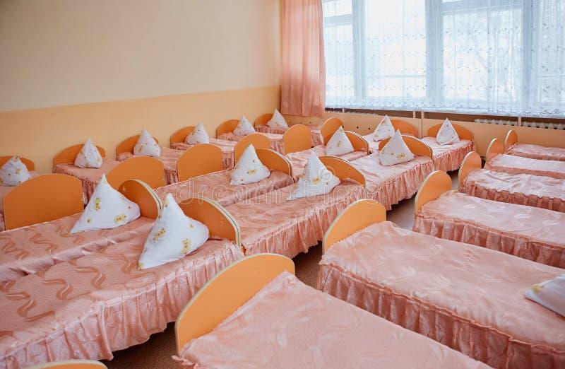 Bedden en wiegen in helder gekleurde slaapzaal van een kinderdagverblijf De wiegen van heel wat kinderen stock foto