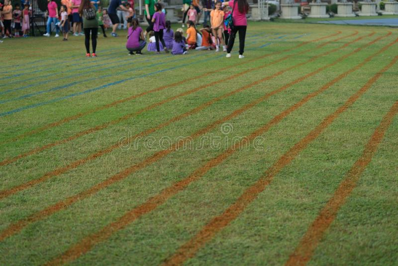 Bedecken Sie Bahn für das Laufen mit Unschärfe an den Läufern im Sportereignis mit Gras lizenzfreies stockbild