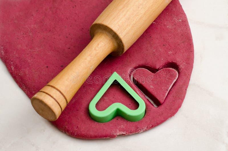 Bedecken Sie roten Teig mit einem Nudelholz- und Plätzchenschneiderherzen und für Valentinstag vorbereiten stockbilder