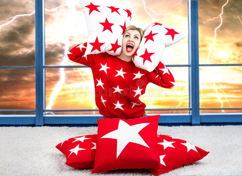 Bedeckungsohren der jungen Frau mit einem Kissen furcht Blitz und Donner im Himmel Kissen für die Hauptinnenverzierung frech lizenzfreie stockbilder