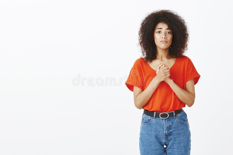 Bedel u me te helpen Portret van knappe krullend-haired vrouw, die handen houden op borst worden dichtgeklemd, die om vergiffenis stock fotografie