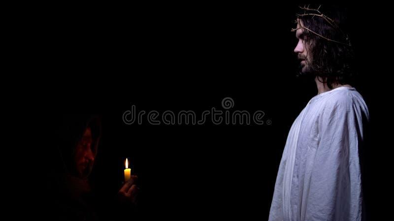 Bedelaar met zoon van kaars de biddende goden, die voor beter toekomstig, christelijk geloof hopen stock foto's