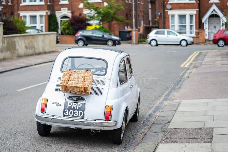 Bedford, Bedfordshire, UK Czerwiec 2 2019 Klasyczny Fiat 500 samochód z pyknicznym koszem na drodze w Anglia strza? za fotografia stock