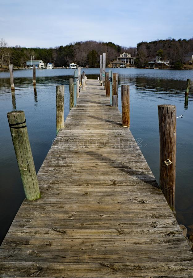 Boat Pier in a Cove on Smith Mountain Lake. Bedford County, VA – January 27th: View of a boat pier located in a cove with vacation homes in the background royalty free stock image
