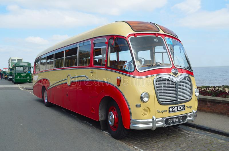 Bedford Super Vega Coach rosso e crema d'annata ha parcheggiato alla spiaggia immagine stock libera da diritti