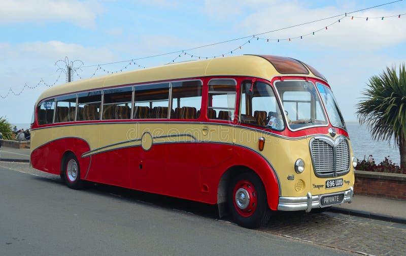 Bedford Super Vega Coach vermelho e de creme do vintage estacionou no beira-mar foto de stock royalty free