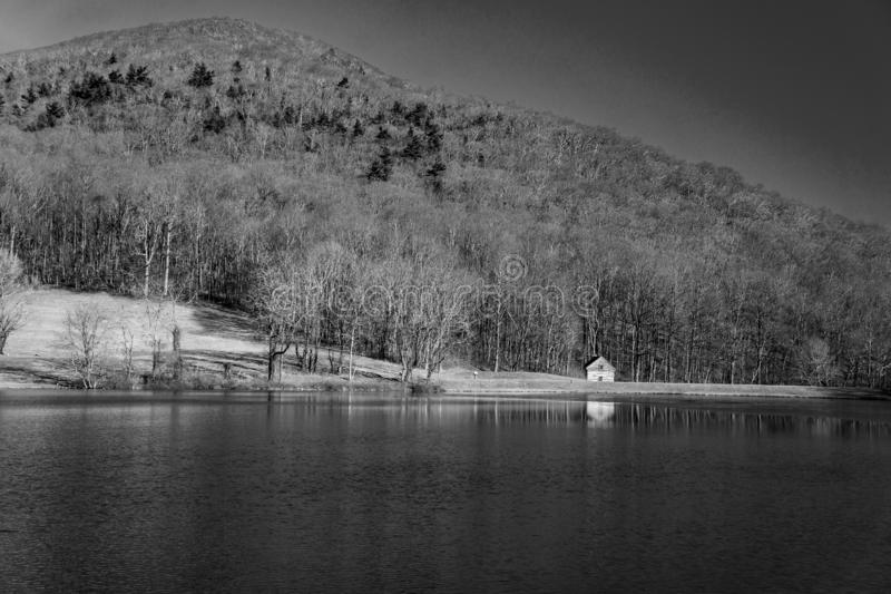 Black and White Image Log cabin at the Base of Flat Mountain stock images