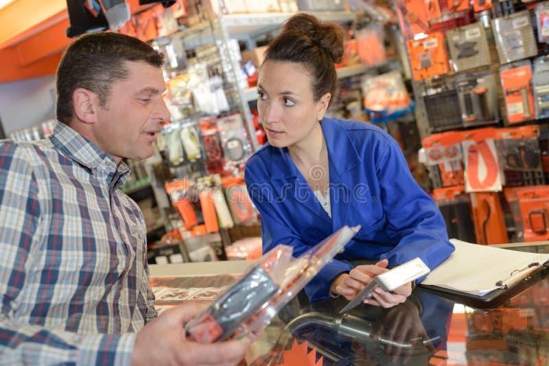 Bediende die klantenprijs op calculator tonen stock fotografie