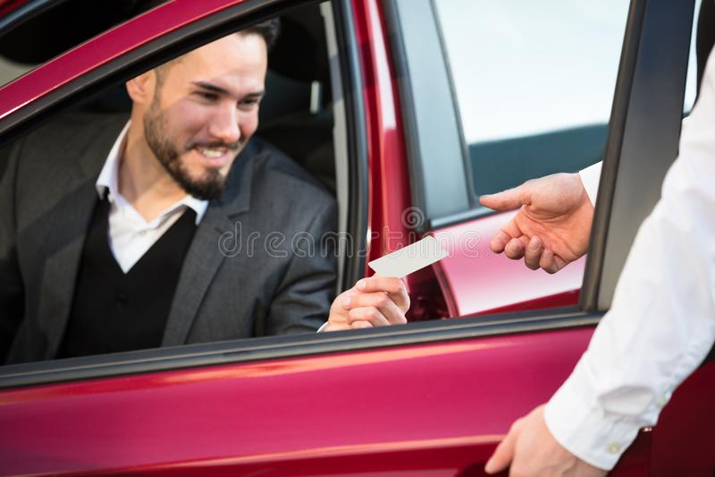 Bediende Giving Receipt To Businessperson Sitting Inside Car royalty-vrije stock afbeelding