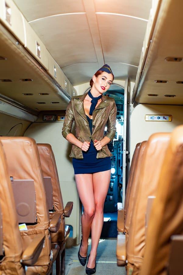 Bediener van de vlucht die wacht tot de passagiers aan boord zijn Portret van glimlachende stewardess in het vliegtuig Luchtvaart stock foto's
