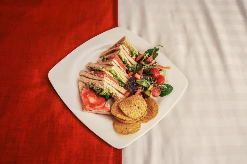 Bediening op de kamer - Vierkante plaat met van de bacontomaat en sla sandwiches en spaanders en saladezitting op een aantrekkeli stock fotografie