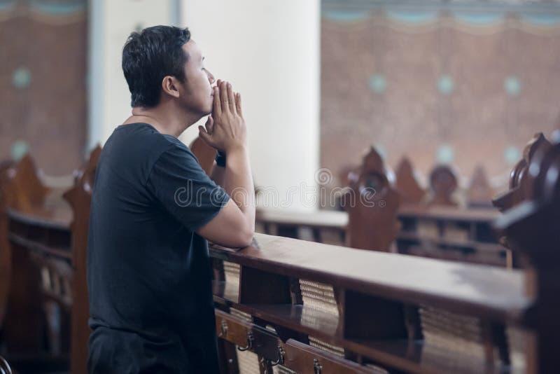 Bedjande förlåtelse för religiös man i kyrka arkivfoton