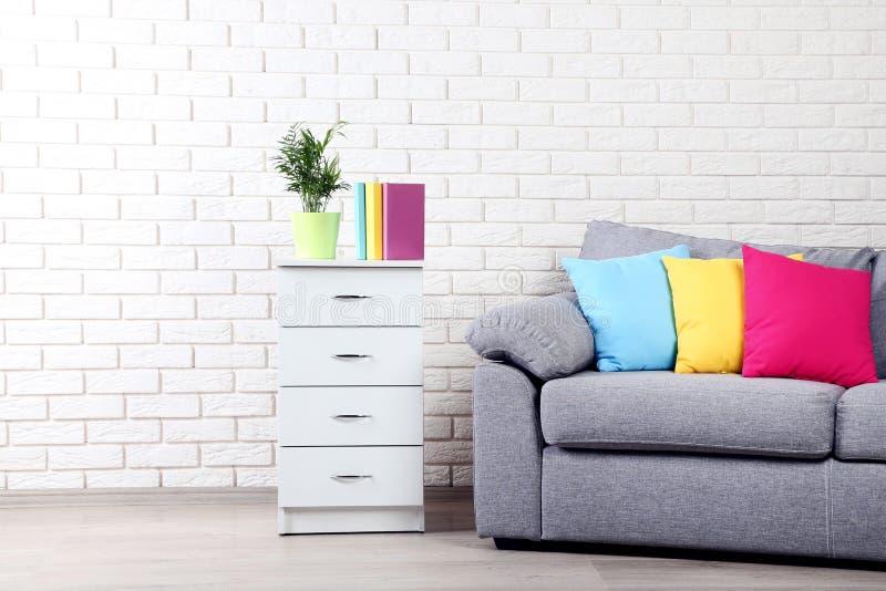 Bedlijst dichtbij bank en kleurrijke hoofdkussens stock afbeeldingen