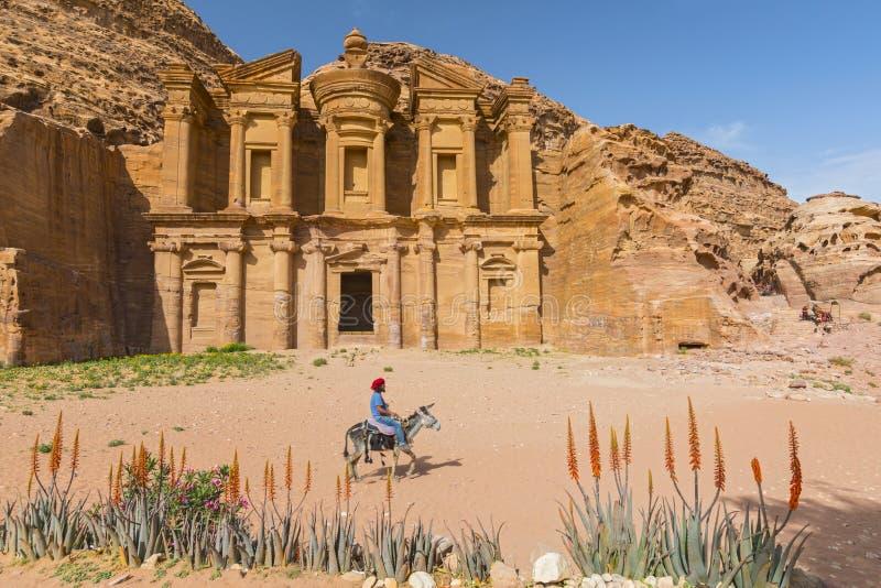Bedouin bij ezel voor het overladen gesneden die rotsgraf als oude de stadspetra van Kloostergr Deir Nabataean wordt bekend, Jord royalty-vrije stock afbeelding