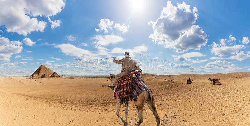 A bedouin on a camel in the desert near the Pyramids of Giza, Egypt stock photo
