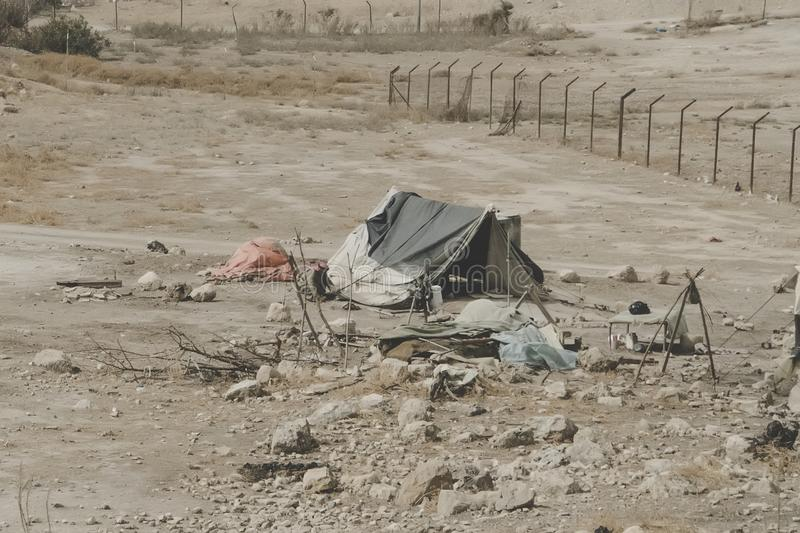Bedouin houses in the desert near Dead Sea. Poor regions of the world. A indigent Bedouin sitting at the tent. Poverty in Jordan. Middle East stock photography