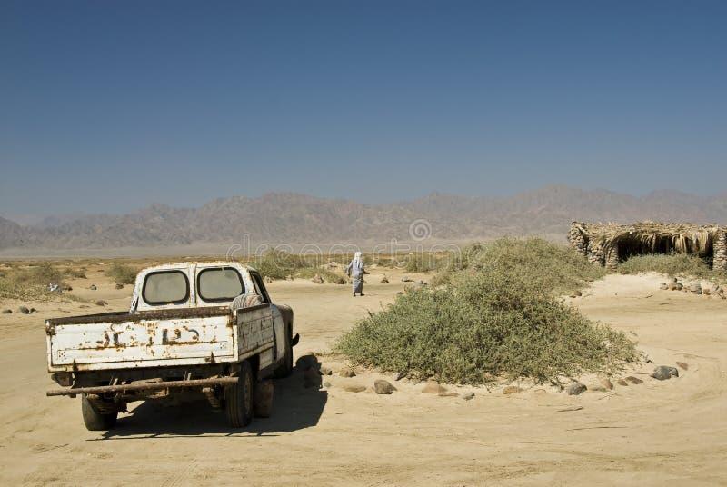 Bedouin man walking away from his truck. stock photo