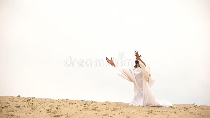 Bedouin raising palms to sky, asking Allah for help and mercy, praying on knees. Stock photo royalty free stock photo