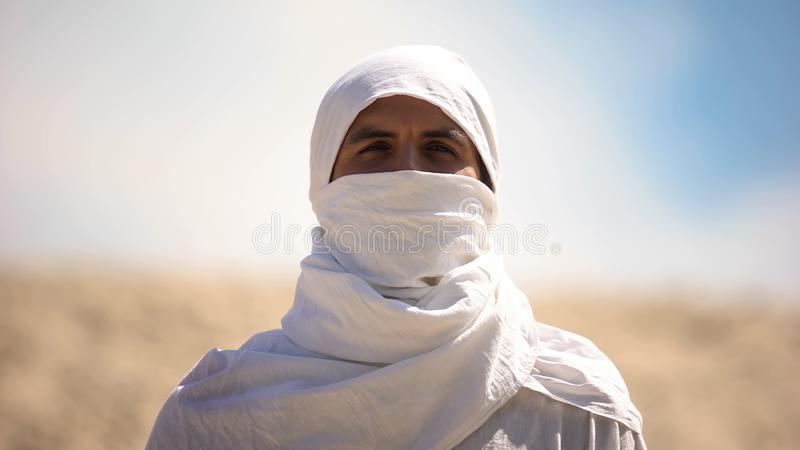 Bedouin in white clothes looking at camera, islamic religion and traditions stock images