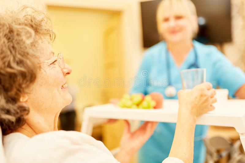Bedridden elderly woman is being cared for royalty free stock photos