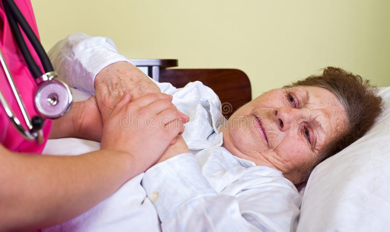Bedridden elderly woman stock images