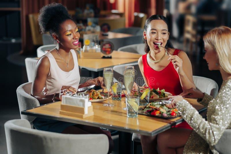 Bedrijf van drie het beste vrienden gerust voelen terwijl het zitten in restaurant stock foto's