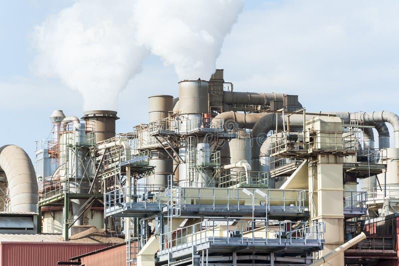 Bedrijf van een meubilairfabriek met rokende schoorstenen stock foto