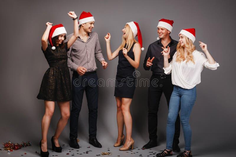 Bedrijf van vrienden in Kerstmankappen het dansen stock foto