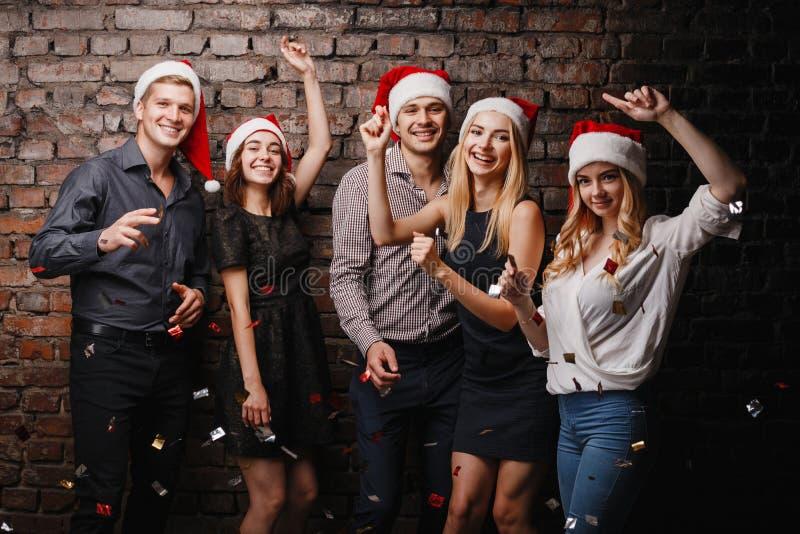 Bedrijf van vrienden in Kerstmankappen het dansen royalty-vrije stock foto