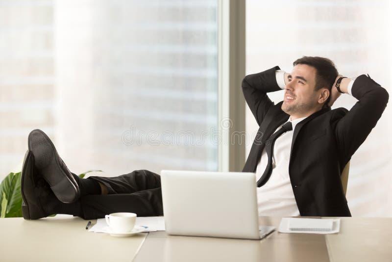 Bedrijfdirecteur het ontspannen bij werkplaats in bureau stock fotografie
