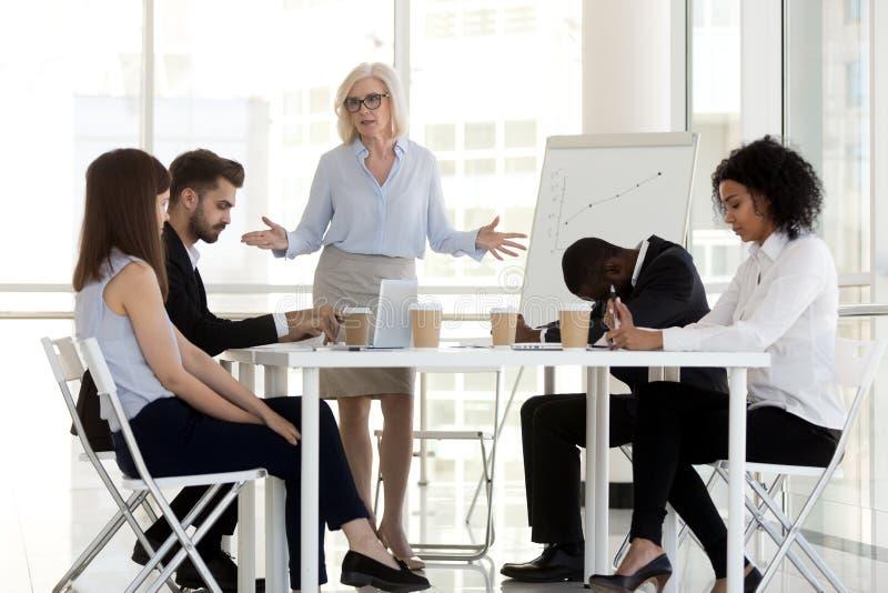 Bedrijfeigenaar die diverse millennial arbeiders in bureau berispen stock afbeelding