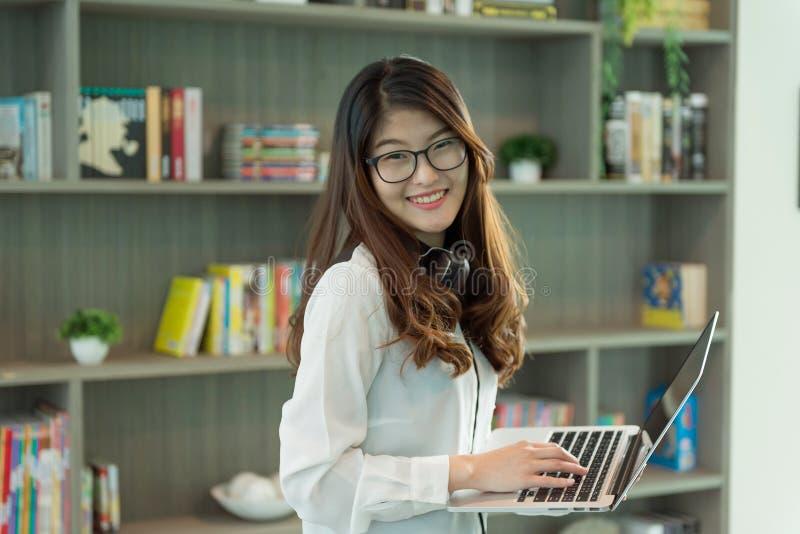 Bedrijfs Aziatisch meisje die laptop in bibliotheek in bureau, persoon met behulp van royalty-vrije stock foto