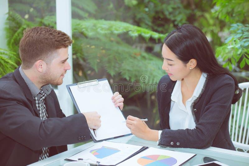 Bedrijfs Aziatische twee mensen die bij bureau zitten die in groepswerk en het bespreken en klembord met contract samenwerken stock afbeeldingen