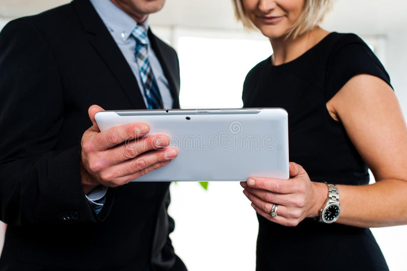 Bedrijfs collega's die op video's op tablet letten royalty-vrije stock afbeelding