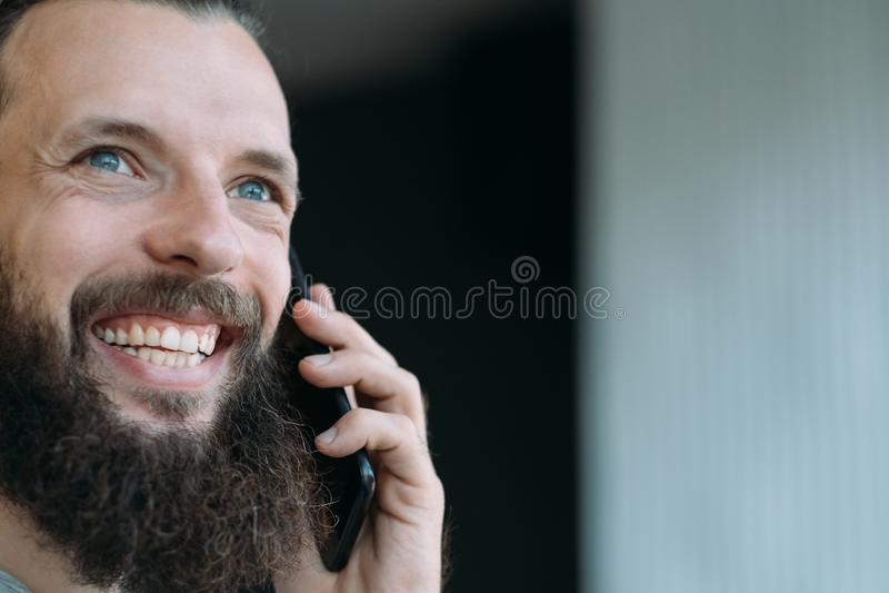 Bedrijfs communicatie het gebaarde kereltelefoon glimlachen royalty-vrije stock afbeeldingen