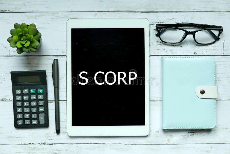 Bedrijfs concept Hoogste die mening van installatie, calculator, glazen, pen, notitieboekje en tablet met S Corp op witte houten  royalty-vrije stock foto