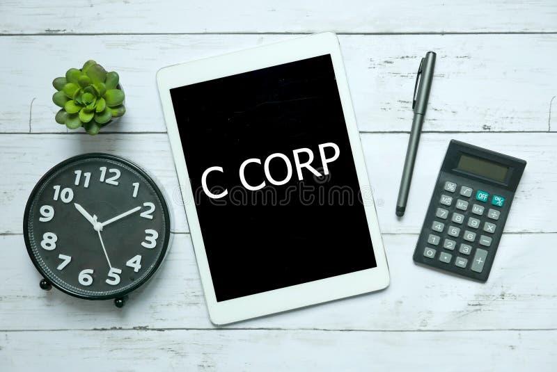 Bedrijfs concept Hoogste die mening van installatie, klok, calculator, pen en tablet met C Corp op witte houten achtergrond wordt royalty-vrije stock foto