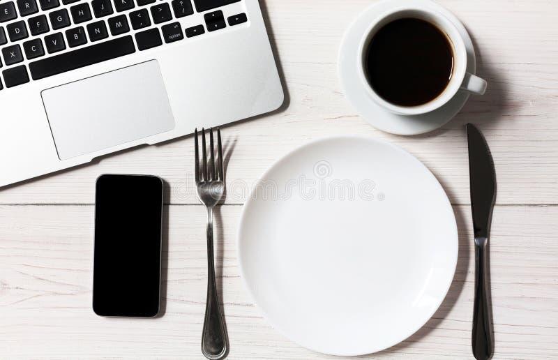 Bedrijfs of dieetconcept, werkplaats met laptop en lege plaat met bestek stock foto's