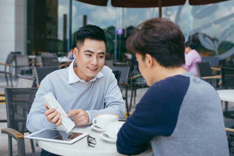 Bedrijfs document bekijken en mensen die terwijl bij koffie bespreken Twee zakenlieden die aan bedrijfsrapport bij koffie samenwe stock foto