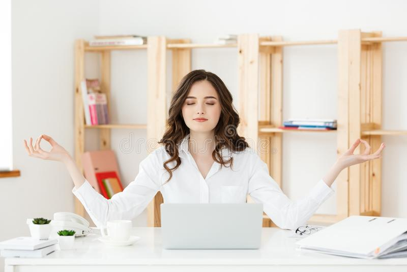 Bedrijfs en Gezondheidsconcept: Portret jonge vrouw dichtbij laptop, het praktizeren meditatie bij het bureau, voor royalty-vrije stock afbeelding